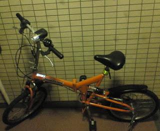 フレームがオレンジ色の折りたたみ自転車