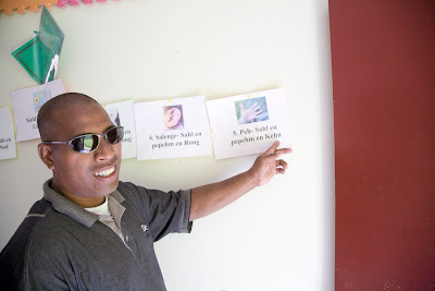 Roddy Robert in dark glasses pointing to information on a school wall