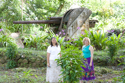 Donna McNear and Mary Kidd in front of a ruined Japanese gun in the jungle