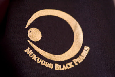 Gold emblem on black cloth, saying Nukuoro Black Pearls, with a logo shaped like a crescent with a pearl in between the two pincers