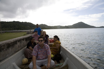 six people in a motorboat alongside a concrete dock, with tropical island in background