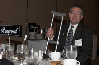 Jim McClurg, seated at a dinner table with crutch