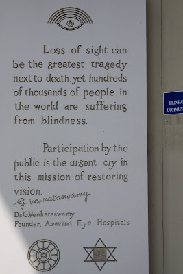 Wall-plaque with the words: <br />Loss of sight can be the greatest tragedy next to death, yet hundreds of thousands of people in the world are suffering from blindness.  Participation by the public is the urgent cry in this mission of restoring vision.  Dr. G. Venkataswamy, Founder, Aravind Eye Hospitals<br />