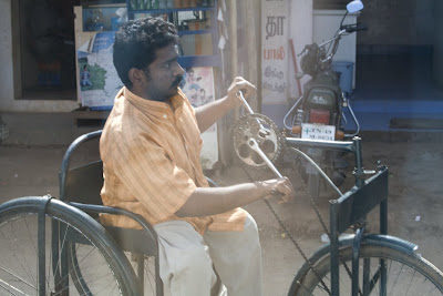 Man using handcrank to power a tricycle