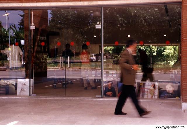 Fotografia di vetrina di negozio con passante al telefono.