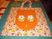 Bolsa de flores y bolsillo frontal naranja con flores cosidas.