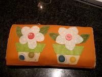 Bolsa de tela plegada decorada con dos macetas en flor en tela.