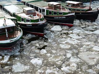 Barkassen im vereisten Hafen von Hamburg mit Eisschollen