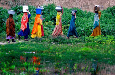 Pakistani women make their way towards their homes after collecting fresh water from a water point on the outskirts of Islamabad, Pakistan