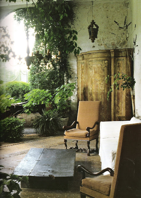 Outdoor living with vine-covered walls, foliage, upholstered chairs, chandelier, hanging lanterns, antique cabinet and white slipcover, image from Timless Interiors by Axel Vervoordt, edited by lb for linenandlavender.net (l&l)