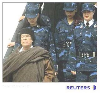 Qaddafi with bodyguards. Image via Reuters.