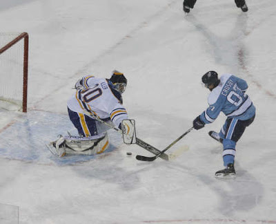 Sidney Crosby of the Pens avoids a poke-check by Sabres goaltender Ryan Miller to score the winning goal in the shootout at the Winter Classic.