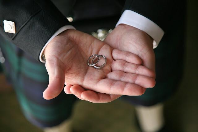 Groom holds wedding rings in his hands
