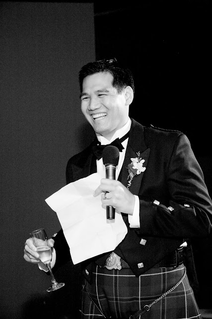 Best man laughing as he toasts bride and groom during wedding reception