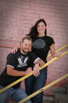 Engagement portrait of couple in front of pink wall in downtown Milwaukee