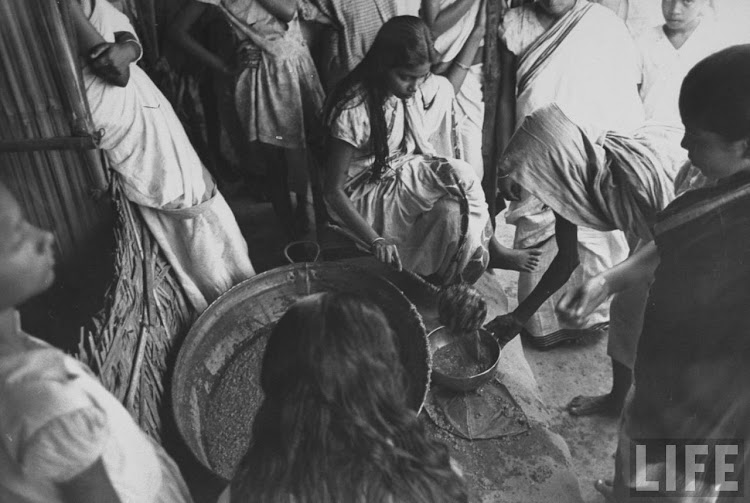 A young Hindu girl serving food to the starving citizens suffering from the famine