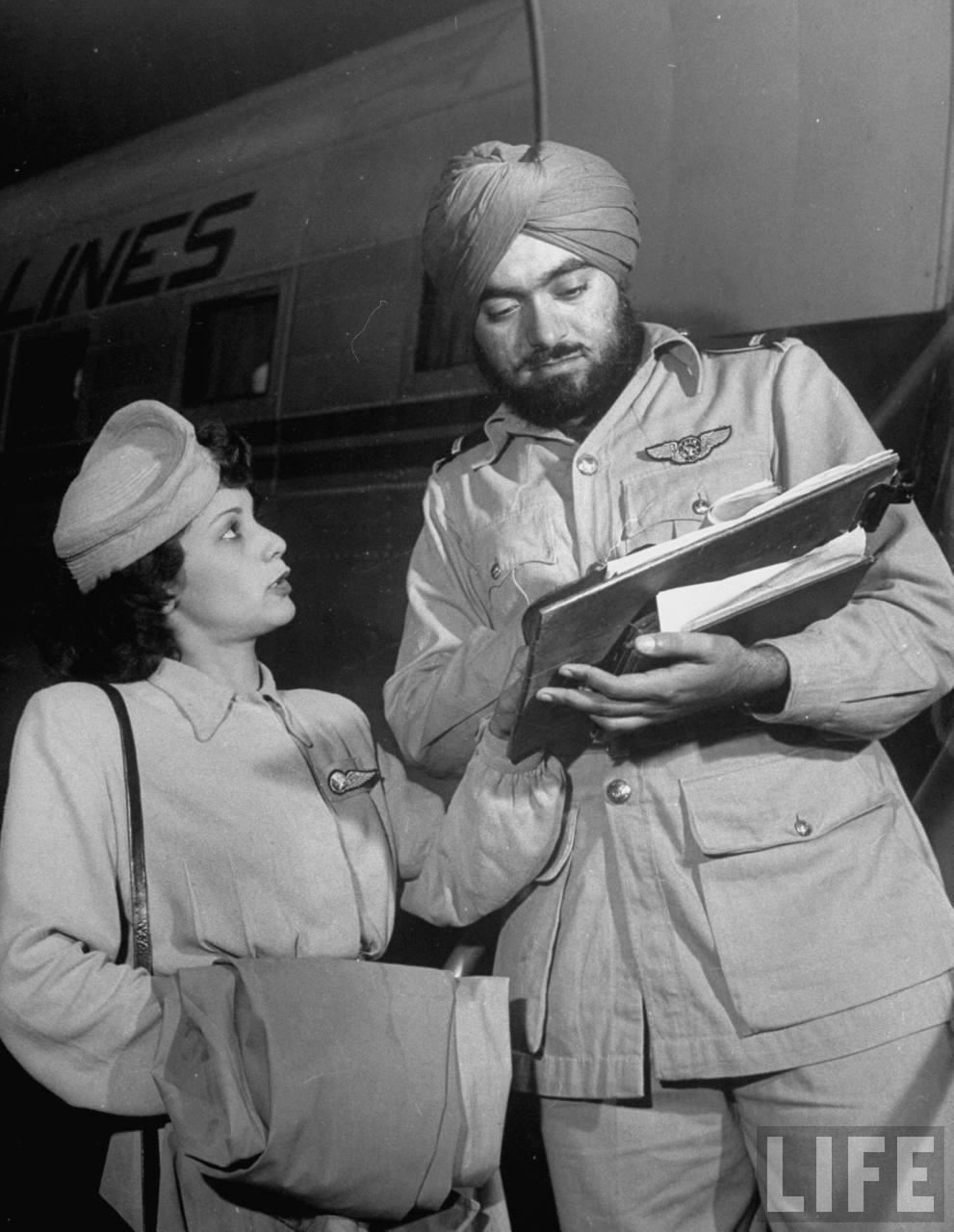 Air India flight attendant Monica Gilbert (L) collecting autograph of publicity dir. Qasi Isa after flight.