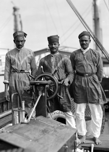 Three Lascars of the 'Viceroy of India', standing behind the wheel of one of the ship's tenders - 1930s