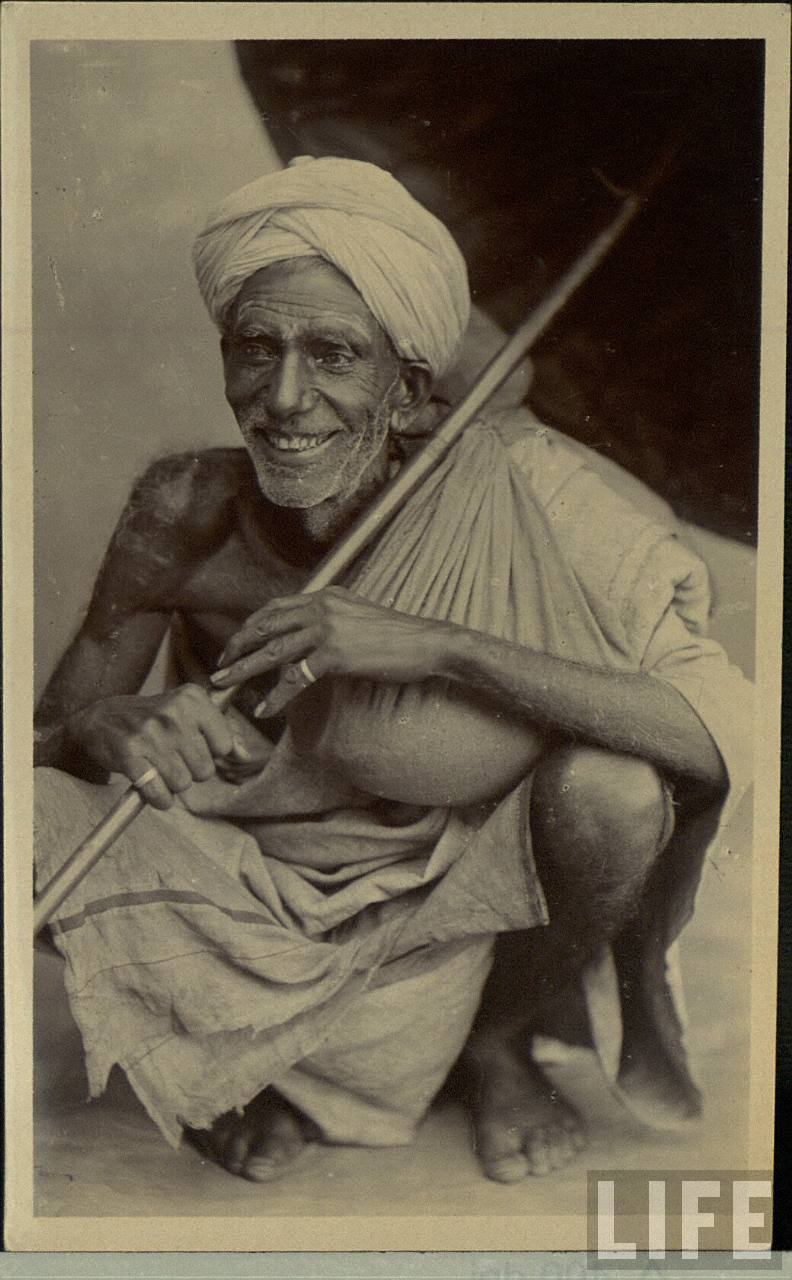 Old Indian Man is Sitting with an Umbrella and Smiling