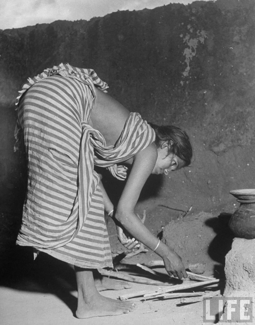 Young woman preparing wood to light fire for cooking in her open area living space - Poodalur India 1946