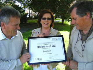 Una Anderson Ryan, Chairperson of the Parkinsons Association of Ireland (PAI), displays Muhammad Ali's Honorary President Award to Billy Rice & Sid Rellis of the Mid-West Parkinsons Association, beneath the shaking leaves of an Aspen Tree – on which the green PAI logo is based.