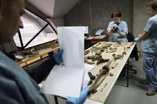 Forensic experts of the International Commission for Missing Persons (ICMP) work at the ICMP centre near Tuzla February 26, 2007 while trying to identify remains of a victim of a 1995 Srebrenica massacre. The highest U.N. court cleared Serbia on Monday of responsibility for genocide in Bosnia during the 1992-95 war, but said it had violated its obligation to prevent and punish genocide.