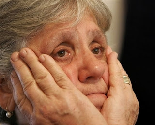 Bosnian Muslim Vasva Smajlovic, 64, reacts during a live TV broadcast from the World Court decision in The Hague, at her the home in the village of Potocari near Srebrenica, Bosnia Monday, Feb. 26, 2007. The United Nations' highest court on Monday exonerated Serbia of direct responsibility for the mass slaughter of Bosnian Muslims at Srebrenica during the 1992-95 Bosnia war, but ruled that it failed to prevent genocide.
