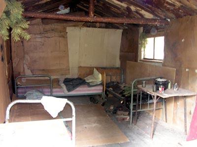 Изба вполне жилая, с кроватями и печкой, а также следами поджога...