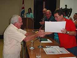 Francisco Rivero Rodríguez, locutor y periodista de Radio Cadena Agramonte, recibe un reconocimiento de manos de Julio César García Rodríguez, primer secretario del Partido Comunista de Cuba en Camagüey