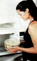 A lady putting food in a microwave oven.