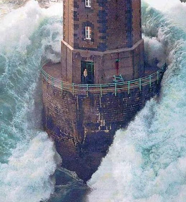 Man in lighthouse, massive wave surrounds the lighthouse.