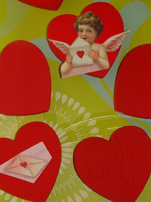 Cutting out vintage images placing them on wood hearts, then decorating them with glitter, ribbon and buttons for ornaments for Valentine's Day. How-To at DearCreatives.com