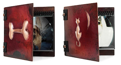 hamdmade photo albums with copper covers - one with a bone, one with a cat and the moon