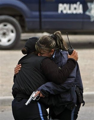 975572535fa2 Two municipal police officers embrace after they were ambushed by unknown  gunmen in the northern border city of Ciudad Juarez