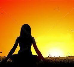 Donna davanti al tramonto nella posizione yoga del loto