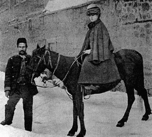 Black and white photo of a woman sat astride a black horse in Tibet. She is accompanied by a local guide.