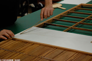Skillful hands putting a thin paper on the wooden frame of shoji, a papered sliding door which allows sunlight into a room, in Kyoto, Japan