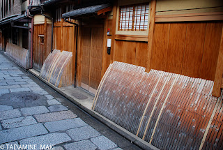 Arched bamboos close to the wooden outer wall, Gion, Kyoto
