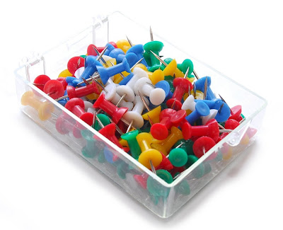 brightly coloured push pins, or map pins in a clear plastic container, copyright J. Gracey Stinson