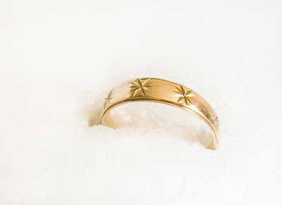 a gold wedding band engraved with stars