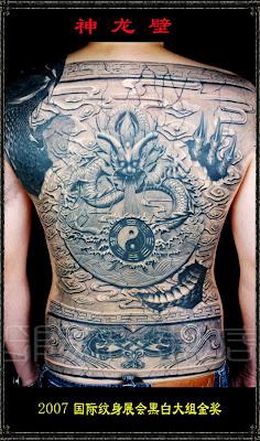 A full back dragon tattoo resembling a wall sculpture.