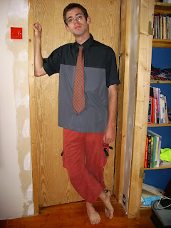 A chap (me) in a black shirt, red trousers which stop above the ankle, and a red tie standing in a doorway.