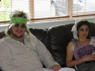 Two oddly dressed people on a sofa.