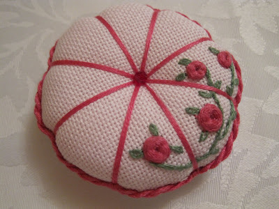 Round embroidered pin cushion decorated with pink roses