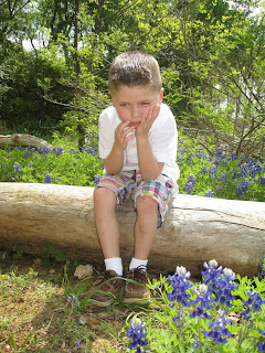 boy sitting on log pouting