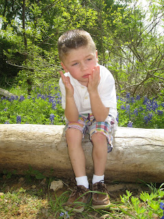 unhappy boy sitting on log