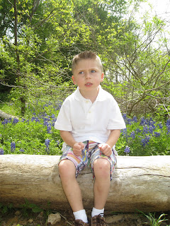 boy sitting on log not looking at camera