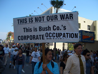 "Photo: sign saying, ""This is not our war, this is Bush Co.'s Corporate Occupation"""