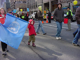Photo: woman and child walking with the flag of the UN
