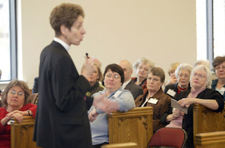 Photo: Katharine Jefferts Schori, Presiding Bishop of the Episcopal Church, speaks before a handful of old people at her church
